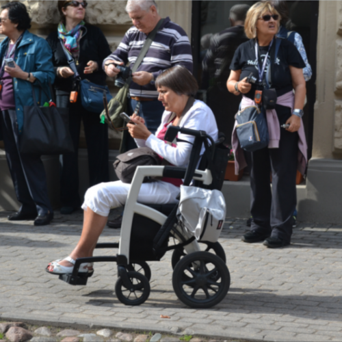 Lady in a cool transport wheelchair checks her smartphone