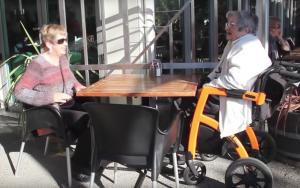 Dame in oranje rolstoel zit met haar dochter op een terras in de zon, waar blijft de koffie?