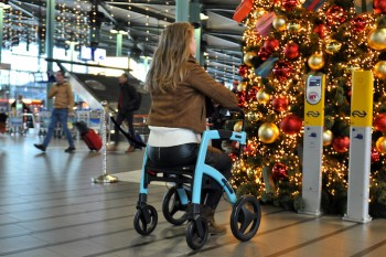 Young lady in airport sitting in a rollator
