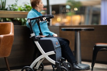 Woman with rollator sitting in a chair at a restaurant