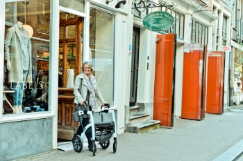 Lady getting out of a shop with a rollator