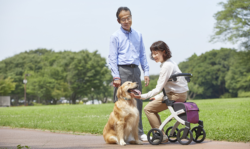 Woman sitting on a Rollz Flex rollator and petting a dog