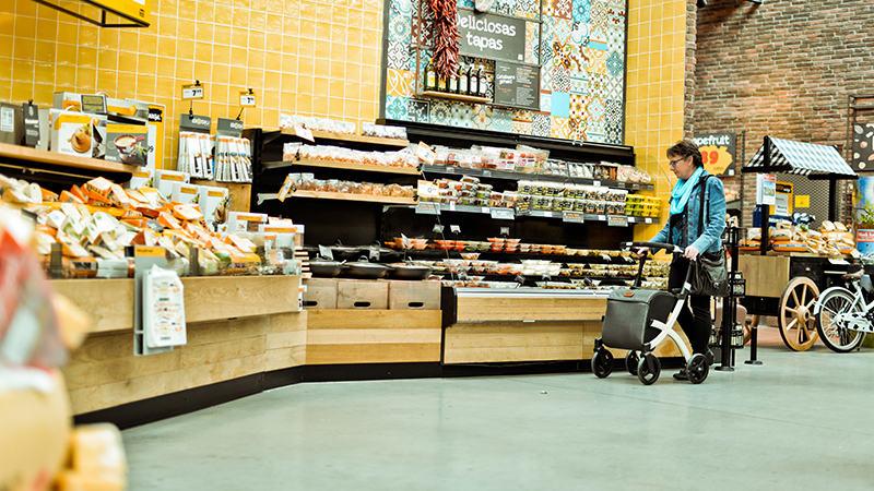 Lady doing groceries in a supermarket with a walker