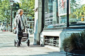 Woman walking with a rollator in a corona safe way on the streets of Amsterdam