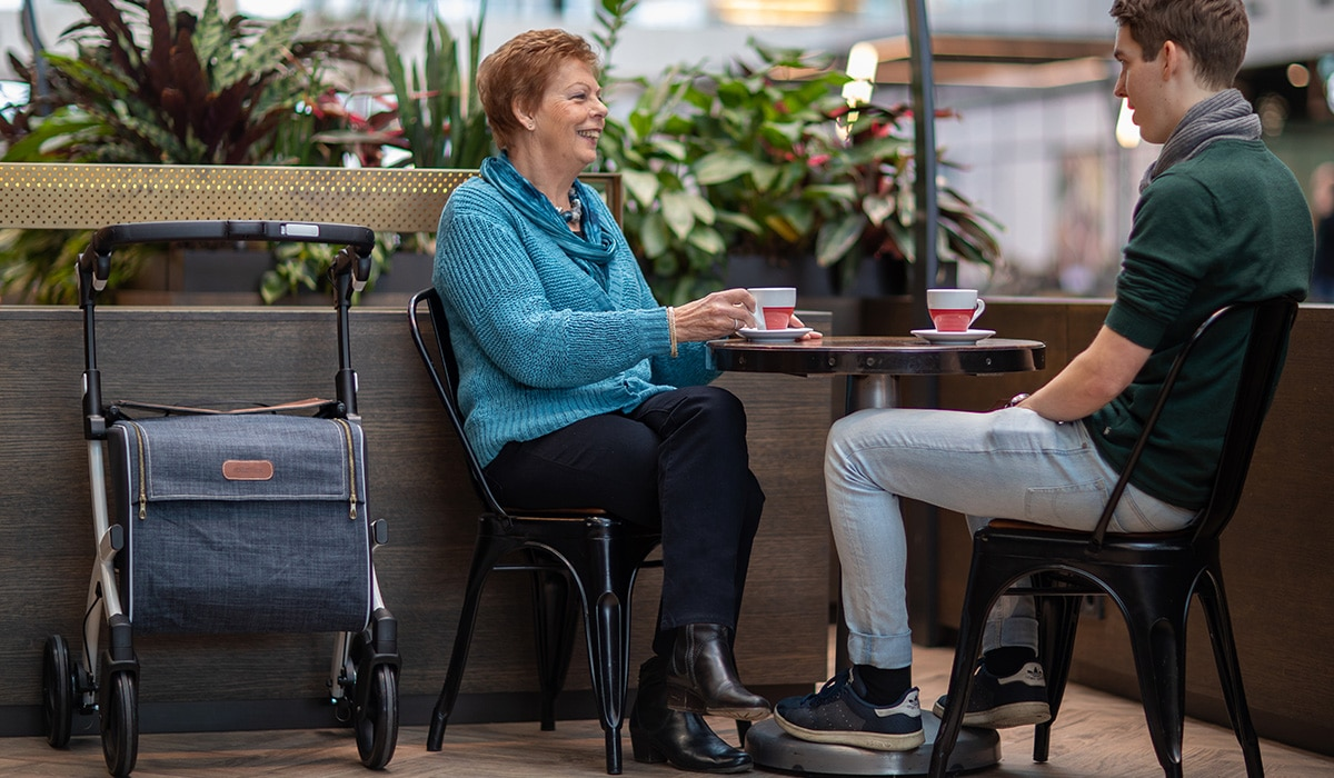 Woman drinking a coffee with her son after walking with a Rollz Flex rollator