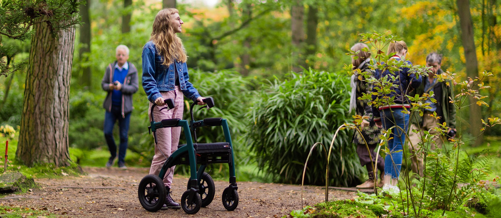 Young girl walking with a Rollz Motion Performance rollator with air tyres in a forest