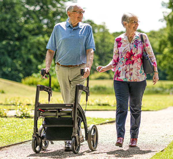 Man with mobility issues walks supported by a Rollz Motion Rhythm Parkinson rollator covered by health insurance