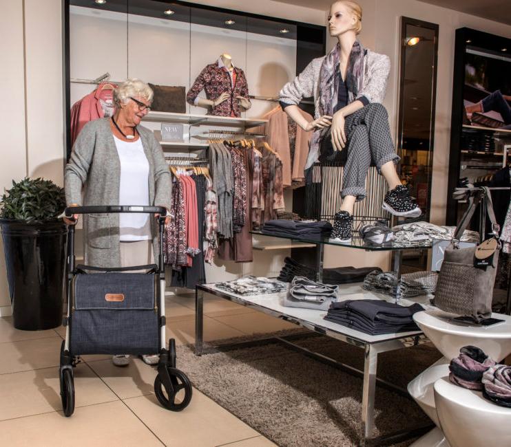 Vrouw gebruikt een Rollz Flex stabiele rollator voor een dagje winkelen
