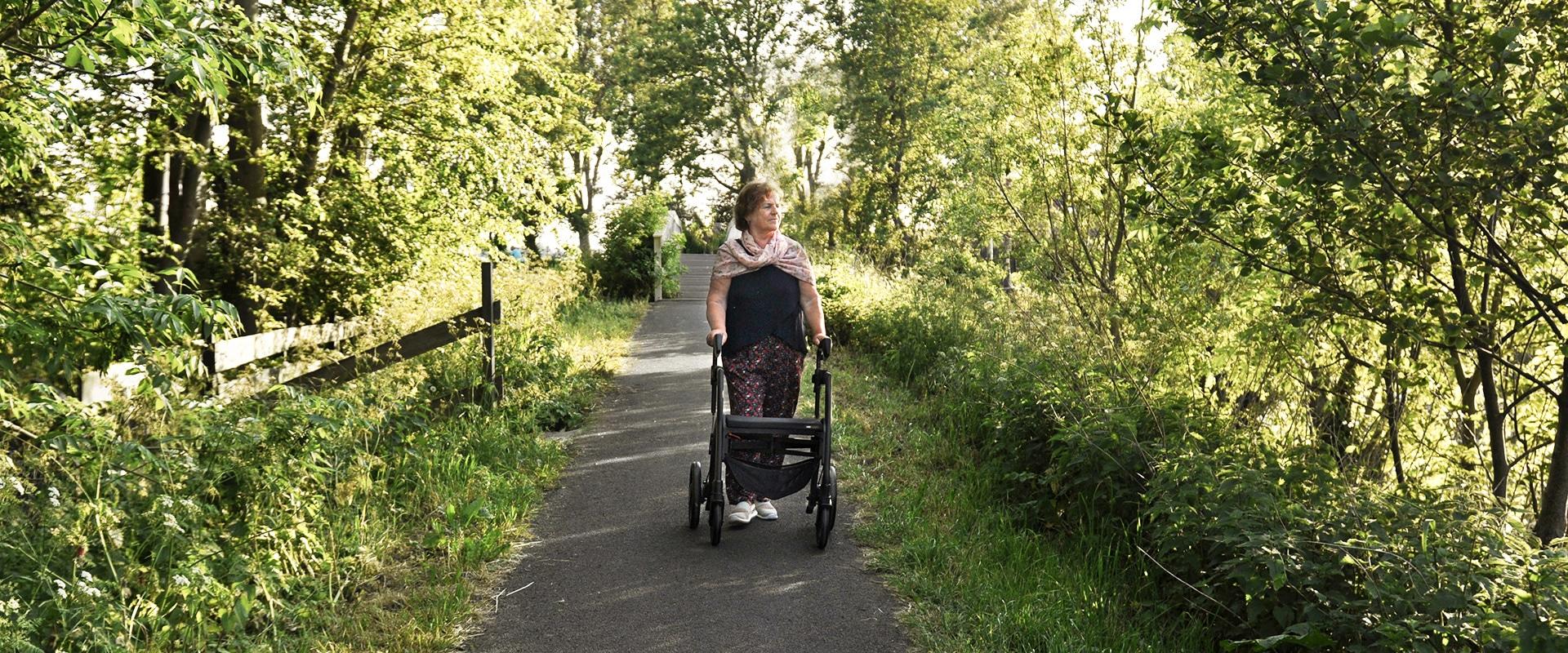 Vrouw loopt met een parkinson-rollator met verstelbare signalen